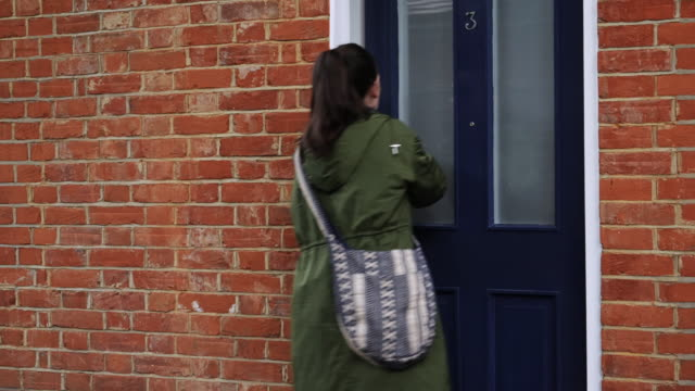Coming home, unlocking the front door. Young attractive woman coming home, unlocking the front door walking indoors, turning the light on and closing the door. It's autumn or fall and he is wearing a coat with a bag over her shoulder. Look for a similar video with spring or summer clothes. Part of a series with same model. front door stock videos & royalty-free footage