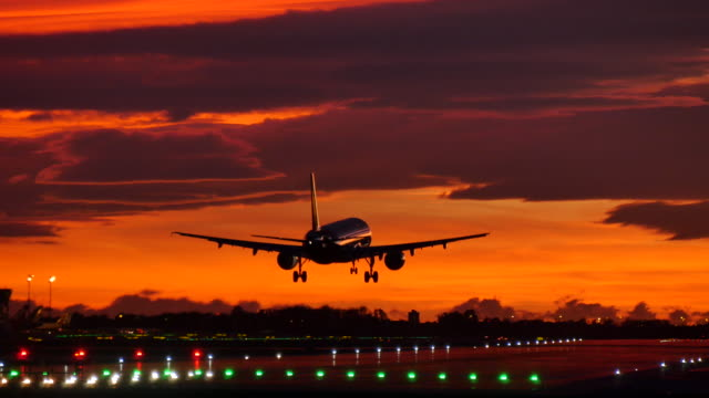 Commercial Aircraft Landing at Barcelona Airport at Sunset Passenger airplane landing under golden sky. airport runway stock videos & royalty-free footage