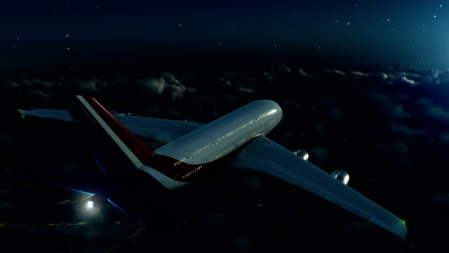 Commercial airplane flying above clouds at night A passenger airliner enters and exist shot above clouds at night over cloudy cityscape free stock without watermark stock videos & royalty-free footage