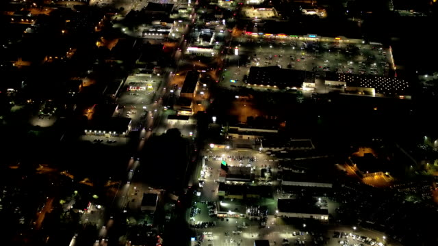 AERIAL: Commercial shopping centers and parking lots lit up with lights at night video