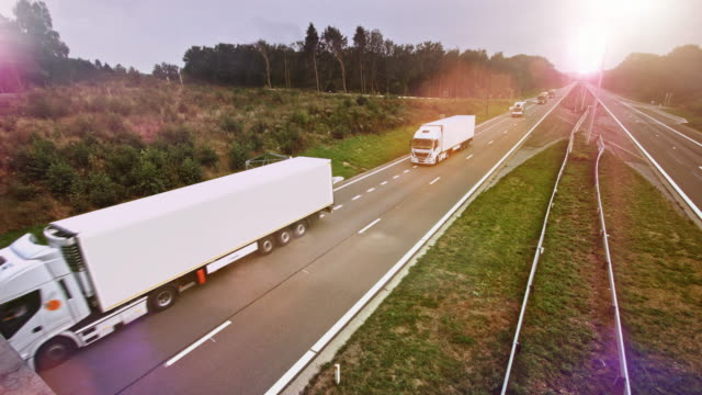 commercial truck with cargo trailer drives through empty highway. sun shining in the background - prodotti supermercato video stock e b–roll