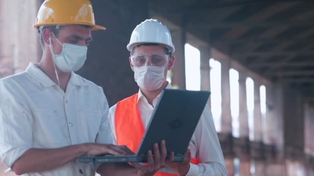 Communication of working personnel in the maintenance and creation buildings. An engineer and a worker are talking at a construction site. Communication of working personnel in the maintenance and creation of buildings. craftsman architecture stock videos & royalty-free footage