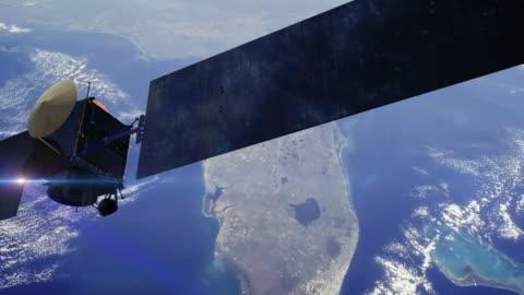 stockvideo's en b-roll-footage met communications satellite orbiting earth - cinematic - gewone snelheid