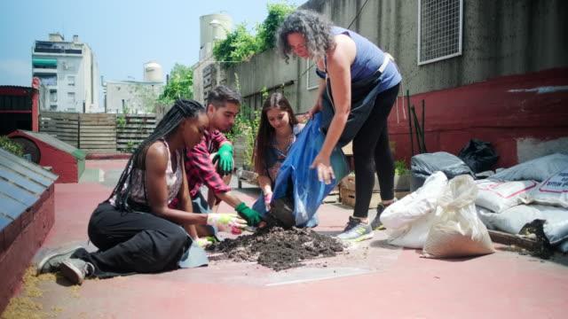 gemeindemitglieder bereiten boden für die bepflanzung im dachgarten vor - urban gardening stock-videos und b-roll-filmmaterial