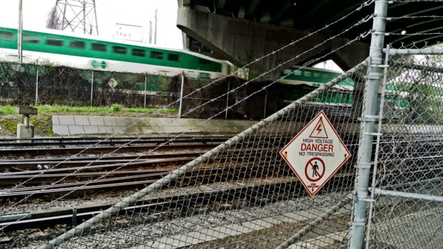 Commuter and subway train pass under bridge with danger sign.