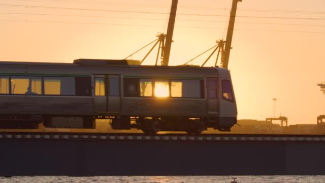 通勤電車がフレアと光で夕日を通り過ぎ、作品や観光客のシルエットを作ります。バックグラウンドで出荷ドックでクレーン。出荷と輸送の概念。パース。 - クレーン点の映像素材/bロール