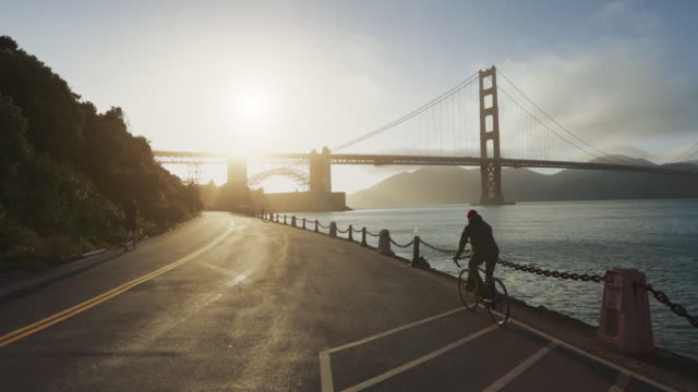 commuter with road racing bicycle and golden gate bridge - motociclista video stock e b–roll