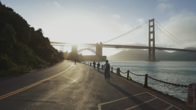 commuter with road racing bicycle and golden gate bridge - ponte sospeso video stock e b–roll