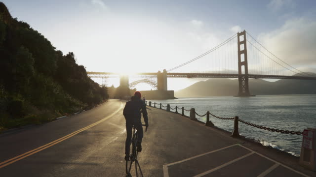 Commuter with road racing bicycle and Golden Gate Bridge Commuter with road racing bicycle and Golden Gate Bridge cycle vehicle stock videos & royalty-free footage