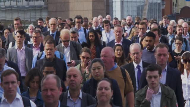 commuters crossing london bridge in the rush hour - большая группа людей стоковые видео и кадры b-roll