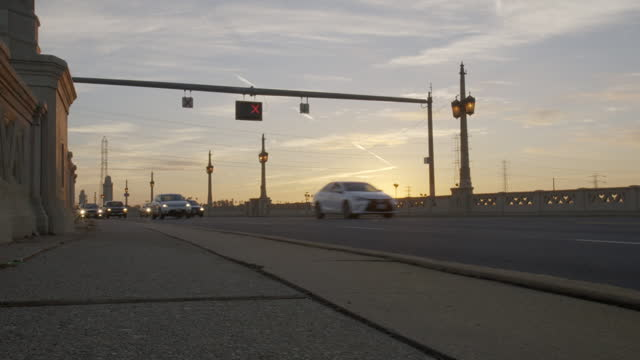 Commuters driving over bridge with sun rising HD video