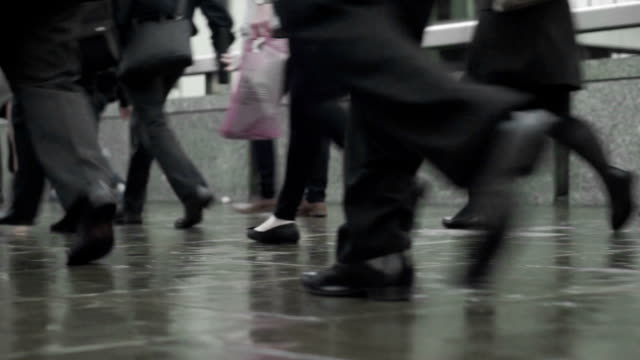 Commuters legs on a rainy street, looped video  COM video