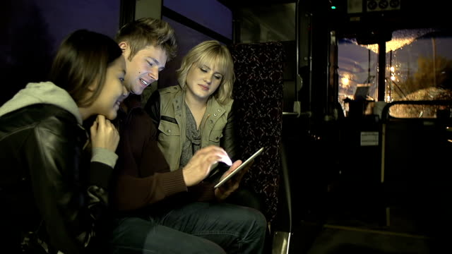 Commuters on a bus playing with digital tablet video