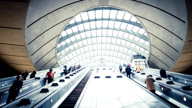 commuters on escalator at subway station canary wharf, docklands london - escalator video stock e b–roll