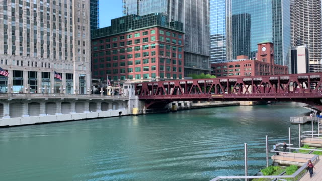 Commuters walk on the riverwalk and ride a water taxi along the Chicago River on spring morning.