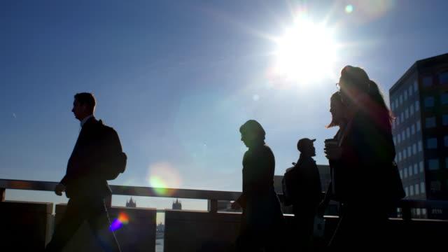 commuters walking, blue sky and sunlight. side view. - london bridge inghilterra video stock e b–roll