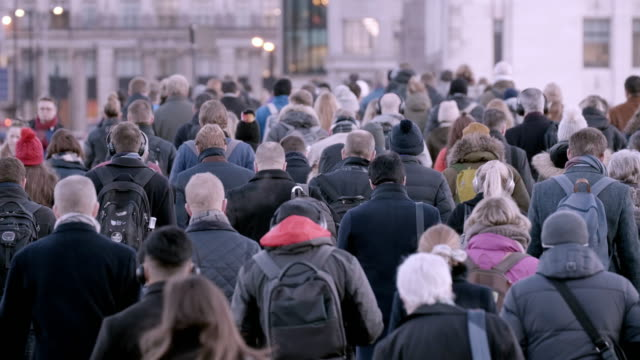 Commuters walking to work, rear view. SM. Crowds of commuters as they cross London Bridge, many wearing hats and warm clothing a large group of people walk to work on a cold winter morning. 60fps. group of people stock videos & royalty-free footage