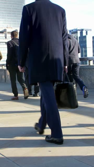 commuters walking to work. vertical format video, slow motion 60fps. - london bridge inghilterra video stock e b–roll