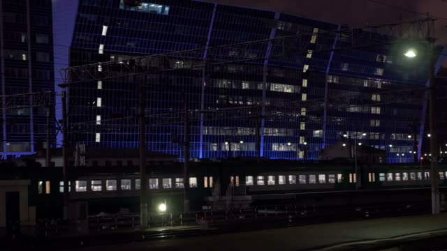 Commuting by train. Evening trip in the city Commuter train passing by open platform in the city at night. Modern illuminated building in background intercity stock videos & royalty-free footage