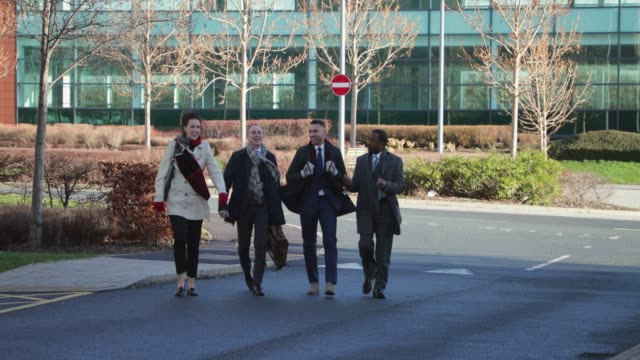 Commuting Coworkers Small group of colleagues are walking through the business park to their office together. office park stock videos & royalty-free footage