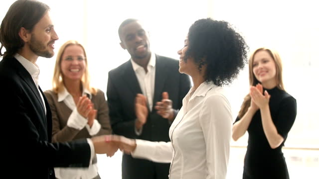 Company boss handshaking african employee, promoting congratulating black young woman video