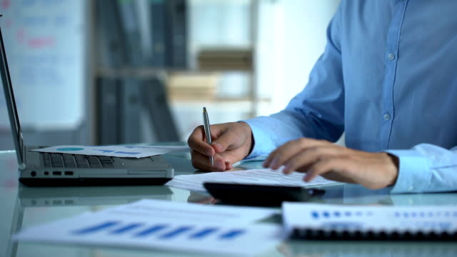 Company marketer counting calculator and filling report, sitting at office table