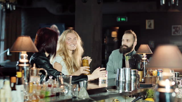 company of 3 happy positive friends celebrating at night bar, clink glasses and fun talking together video