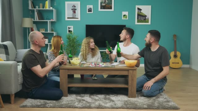 Company of boys and girls playing board game in living room and drinking beer video