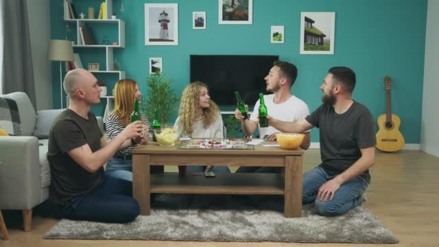 gesellschaft von jungen und mädchen spielen brettspiel im wohnzimmer und trinken bier - bauholz brett stock-videos und b-roll-filmmaterial