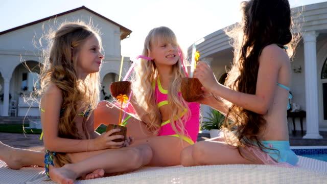 glada vänners med kokosnötter i händer relax poolen, cocktail party lite flickvänner, lycklig barndom - birthday celebration looking at phone children bildbanksvideor och videomaterial från bakom kulisserna