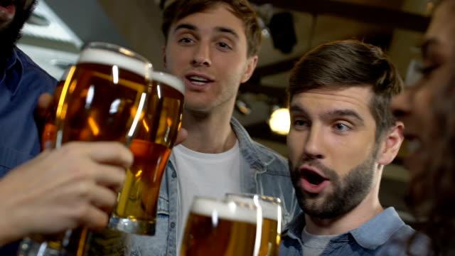 幸せな人々の会社クリックしビールグラス、週末に友人とリラックス - バーカウンター点の映像素材/bロール