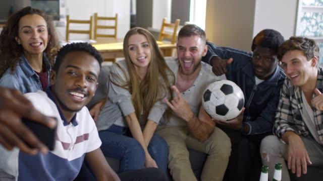 vídeos de stock e filmes b-roll de company of soccer fans taking selfie together at home - soccer supporter portrait