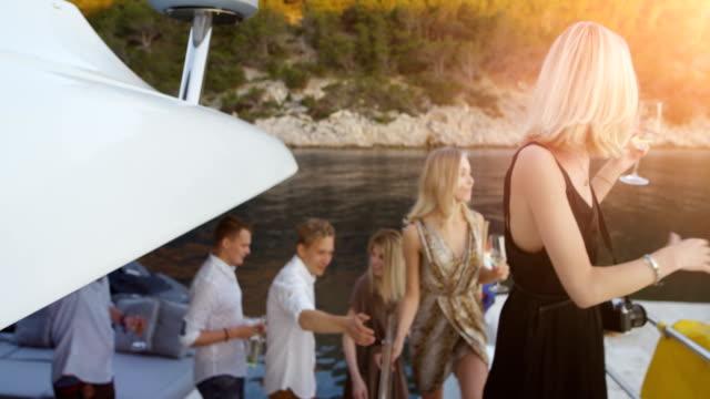 vídeos y material grabado en eventos de stock de compañía de niñas y niño en ropa de fahionable licencia yate a parte. vista de playa hermosa y gente feliz. - yacht