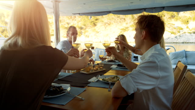 company of young people on a yacht, they clink glasses in celebration. table served with steamed mussels. beautiful seaside view. - seafood stock videos and b-roll footage