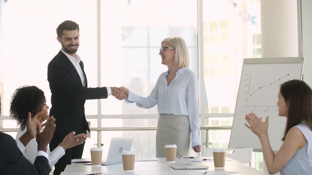 Company staff applauding while director greeting handshakes with new employee In modern boardroom gathered multi-ethnic business people, company staff sitting at table clap hands while director shaking hands new employee or greet business coach show gratitude thanks for seminar promotion employment stock videos & royalty-free footage