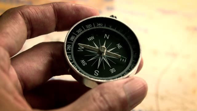 Compass in hand against the map background Compass in hand against the map background navigational compass stock videos & royalty-free footage