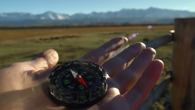 Compass in hand at mountains terrain