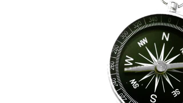 Compass Pointing North A black and silver compass on a white background pointing north. navigational compass stock videos & royalty-free footage