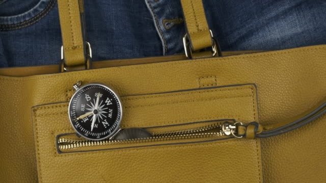 Compass sticks out of the pocket of a female bag. Approaching, crane shot. Travel concept.