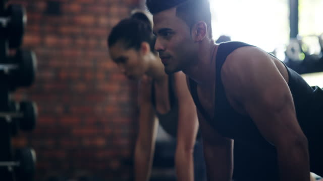 konkurrerar med varandra som kan göra mer push ups - gym skratt bildbanksvideor och videomaterial från bakom kulisserna