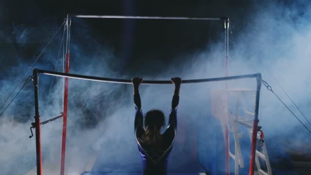 vídeos y material grabado en eventos de stock de competiciones en gimnasia. una mujer camina hacia el travesaño y realiza dips chanclas en cámara lenta sobre un fondo oscuro en retroiluminación. cámara lenta - gimnasia