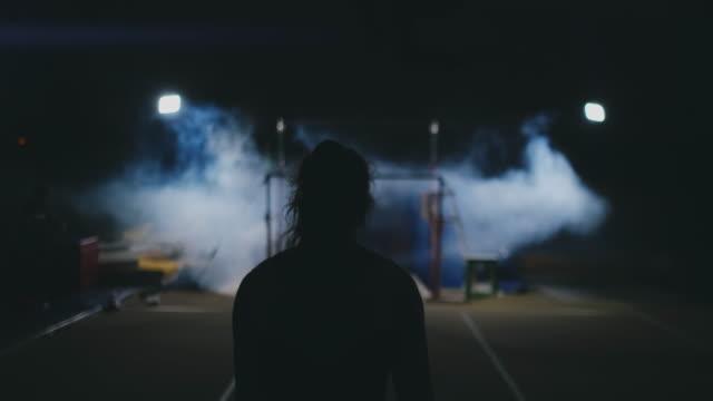 wettbewerbe in der gymnastik. eine frau geht an die querstange und führt in zeitlupe auf dunklem hintergrund im hintergrundlicht dips-flops durch. zeitlupe - turngerät mit holm stock-videos und b-roll-filmmaterial