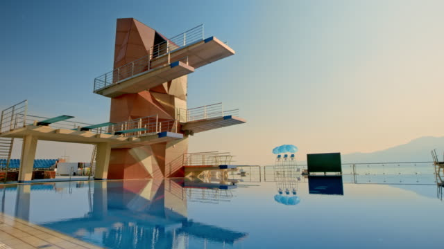 CS Competitive diving tower above an empty pool at sunset
