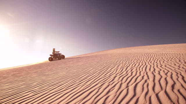 competitive quadruplo motociclista calciare up durante il viaggio fino duna di sabbia - bike tire tracks video stock e b–roll