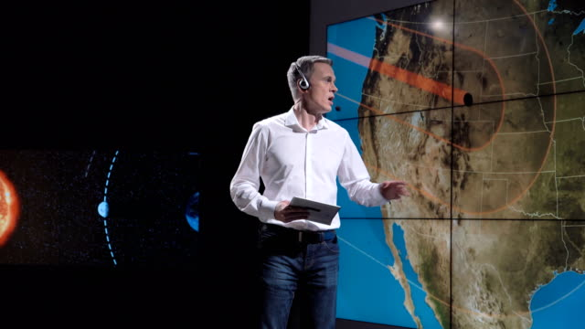 Competitive scientist speaking about natural phenomenon A news weather reporter forecasting a solar eclipse on a futuristic television set. Elements of this image furnished by NASA. meteorology stock videos & royalty-free footage