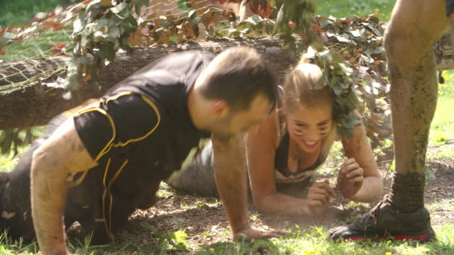 Competitors help each other through net on an assault course video