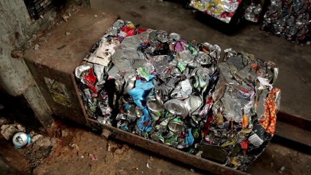 raccolta di lattine riciclate schiacciato bales in stagno - alluminio video stock e b–roll