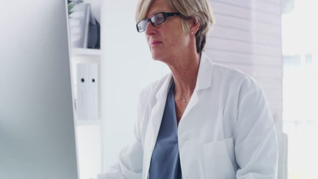 Compiling new patient reports 4k video footage of a mature doctor working on a computer in her office female doctor stock videos & royalty-free footage