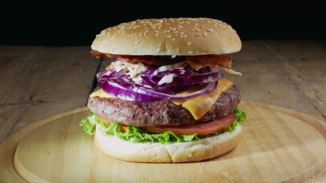 complete burger on rotating plate - cheeseburger filmów i materiałów b-roll