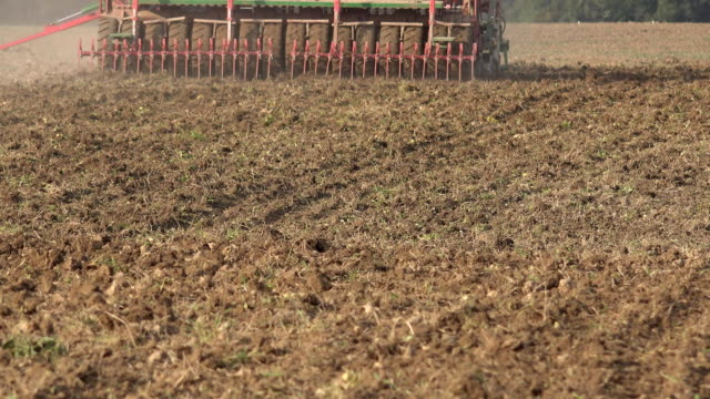 Complex seeder sower equipment cultivate sow crops in soil. FullHD Complex seeder sower equipment cultivate sow crops in fertile soil. Static shot. FullHD sowing stock videos & royalty-free footage